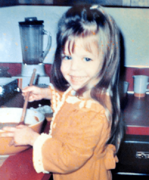 a young girl with long brown hair in a gold robe standing at the counter stirring pumpkin pie filling in a large yellow mixing bowl.