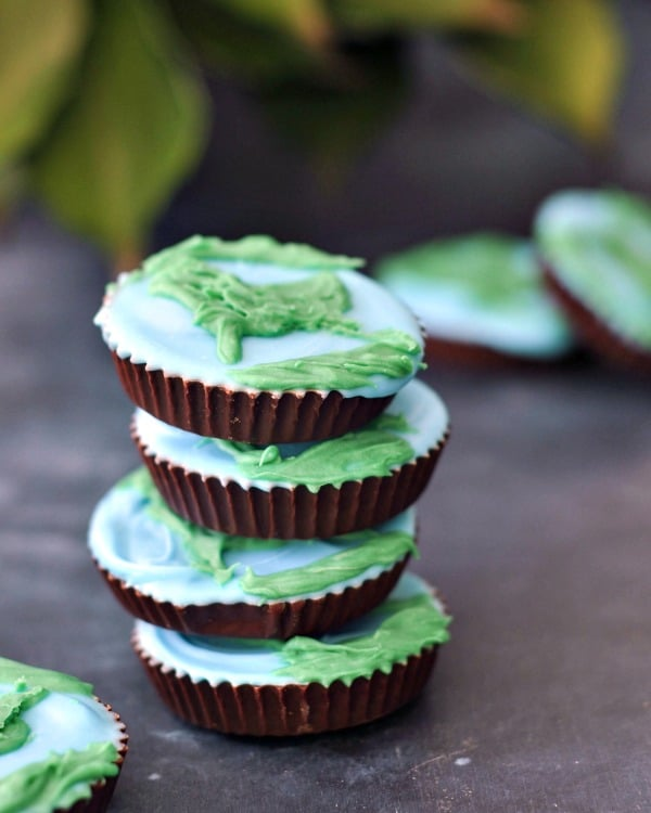 close up stack of peanut butter cups decorated as blue and green earths for Earth Day