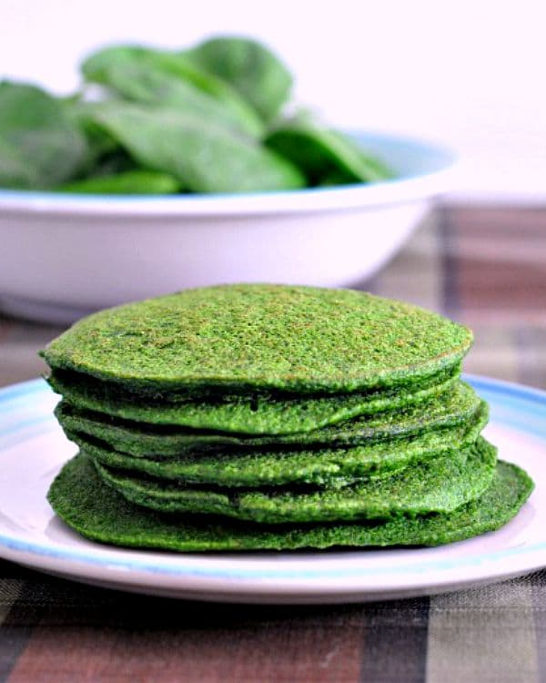 Spinach Pancakes stacked on a plate, bowl of fresh spinach in background
