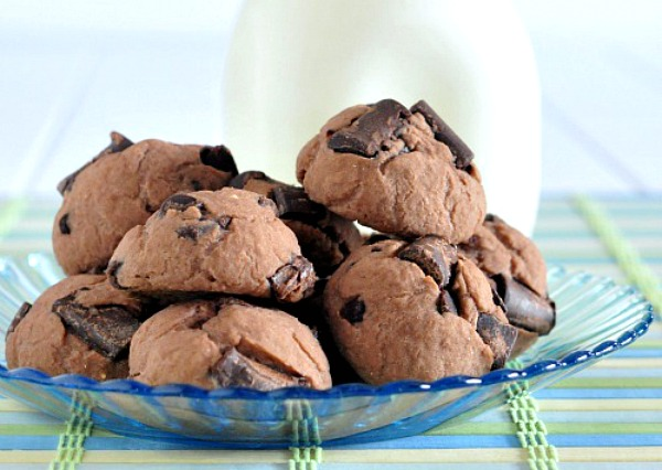 Double Rich Chocolate Protein Cookies piled on plate, bottle of milk on side