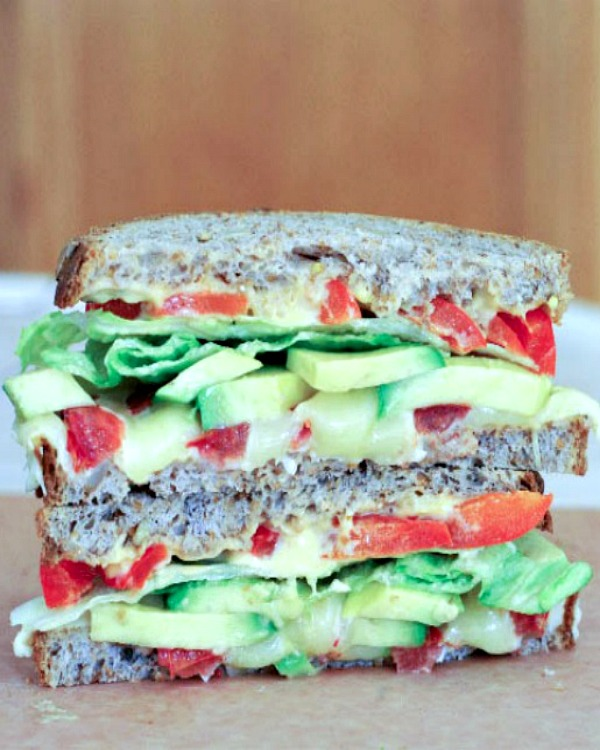 Grilled Cheese Sandwich with avocado, tomatoes, lettuce, one half stacked on top of other half