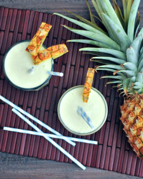 overhead view of vegan cocktails - two Pina Coladas and a pineapple