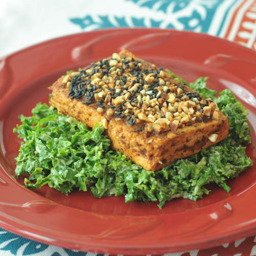 Marcona Crusted Tofu over kale on a plate