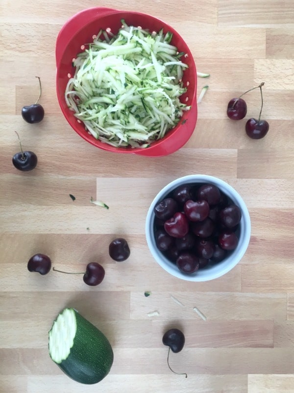 How To Make Vegan Zucchini Muffins: bowls of fresh grated zucchini and pitted cherries on a butcher block