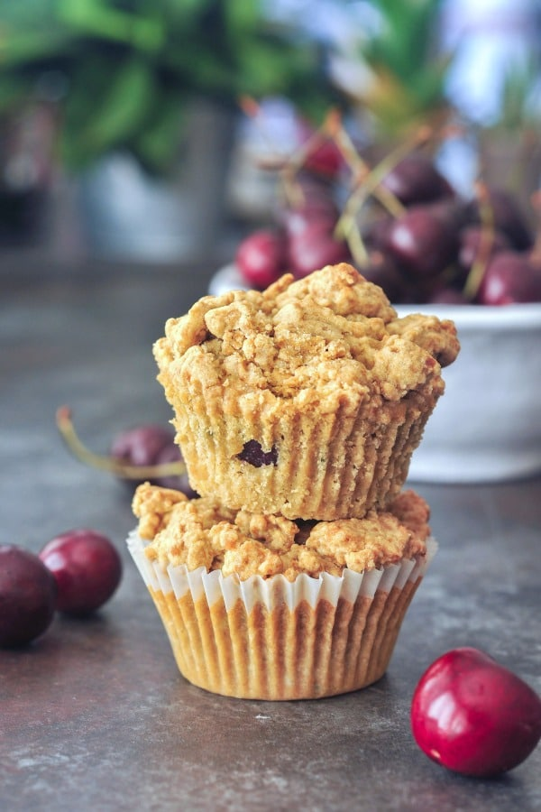 cherry zucchini muffins with a bowl of fresh cherries in the background