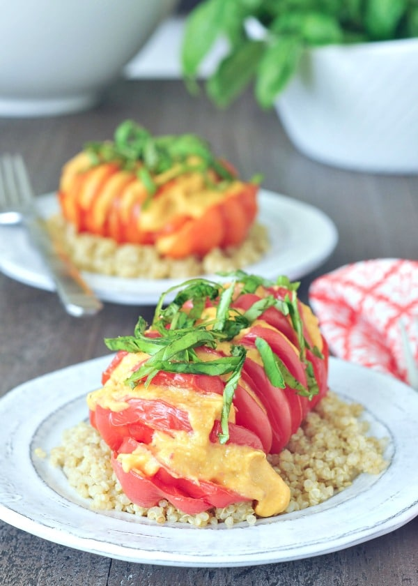 Cheesy Roasted Hasselbackhow to hasselback - bright red tomato sliced hasselback style, with melty cheese and fresh chopped basil, served over quinoa