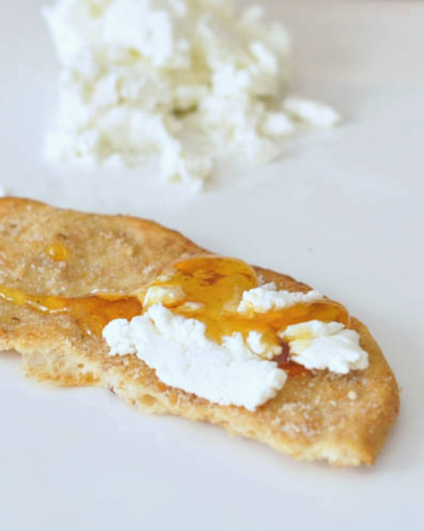 Vegan Goat Cheese spread on a cracker with maple syrup
