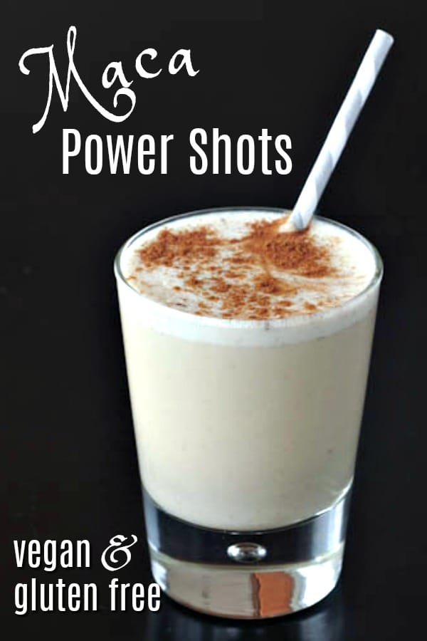 light colored Maca Power Smoothie in a small glass with a straw and cinnamon sprinkled on top, against a black background