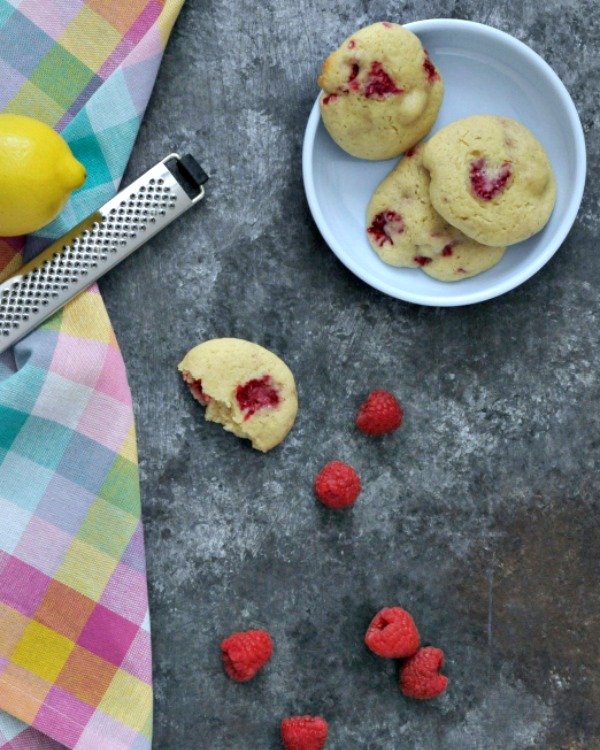 Raspberry Lemon Cheesecake Cookies on a plate, fresh raspberries, a lemon and zester nearby