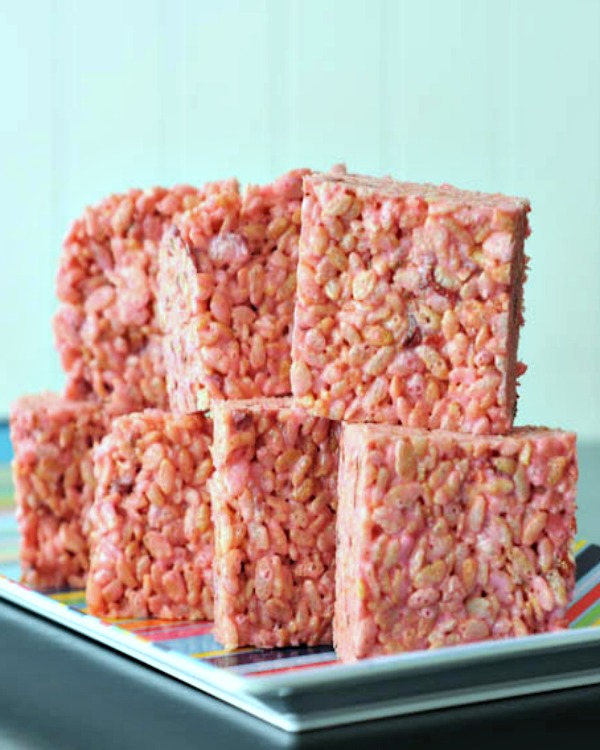 pink Strawberry Lemon Rice Crispies squares stacked on a plate