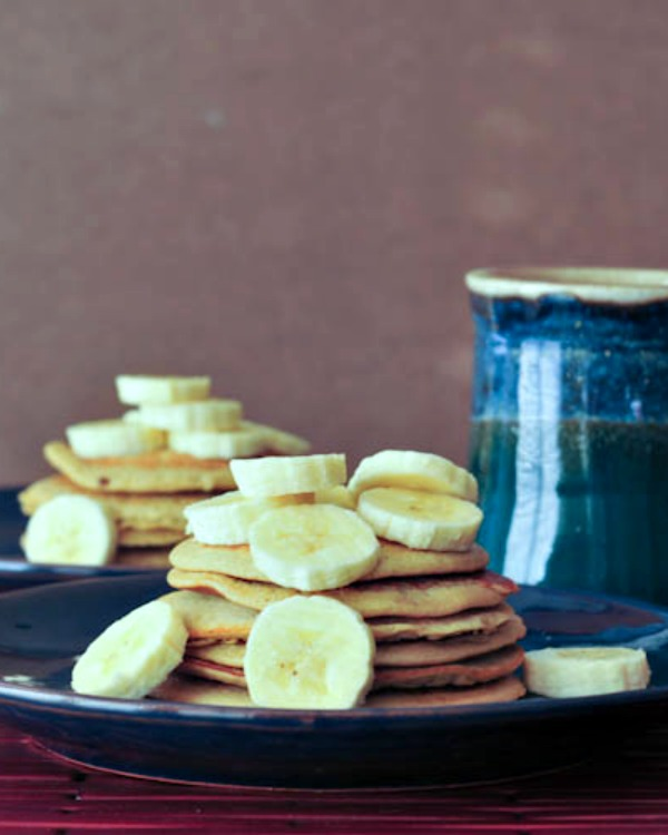 tall stack of Banana Maca Pancakes with sliced bananas, cup of coffee on side