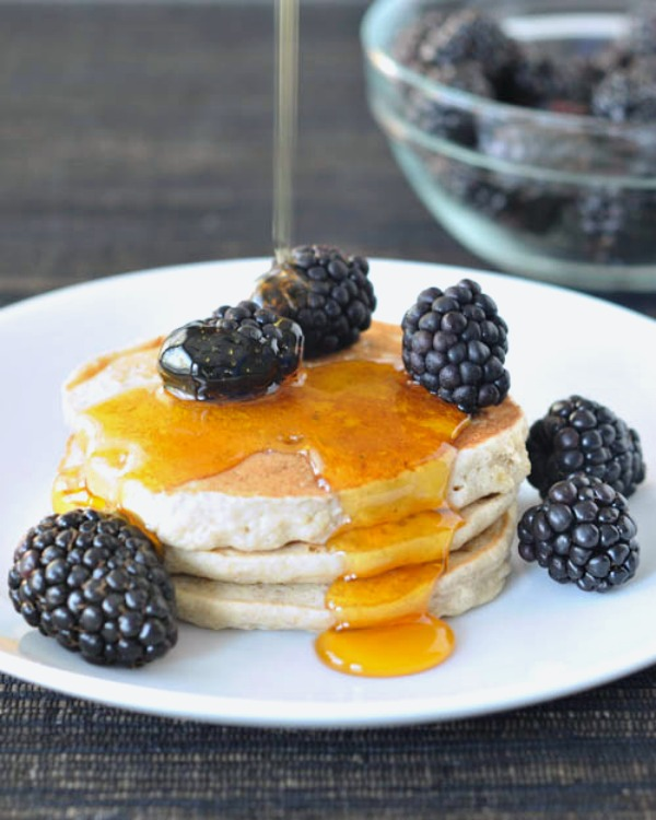 Buckwheat Hemp Banana Pancakes stacked on a plate with fresh blackberries and syrup being poured over top