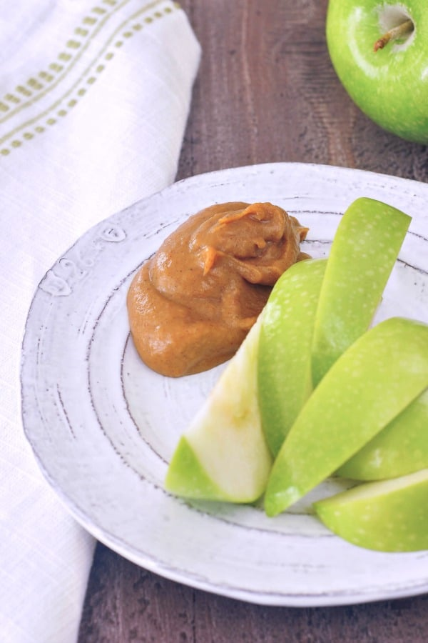 a dollop of Pumpkin Caramel Sauce on a plate with green apple slices