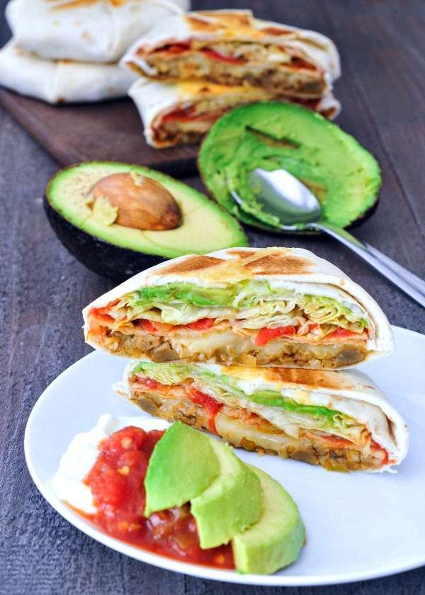 Homemade Crunchwrap Supreme on a plate, sliced in half with avocado and salsa on the side
