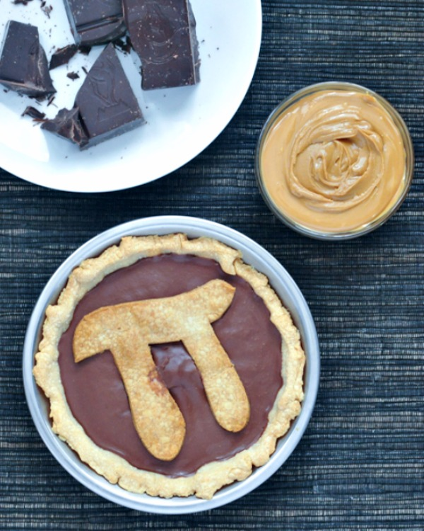 Chocolate Peanut Butter Truffle Pie with Pi symbol in crust on top, chopped chocolate and small bowl of peanut butter on side