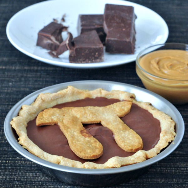 Chocolate Peanut Butter Truffle Pie with Pi symbol in crust on top, chopped chocolate and small bowl of peanut butter in background