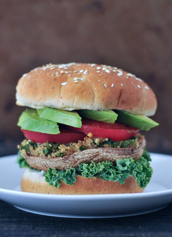 Garlic Kale Stuffed Portobello Burgers stacked on a bun with lettuce, tomato, avocado