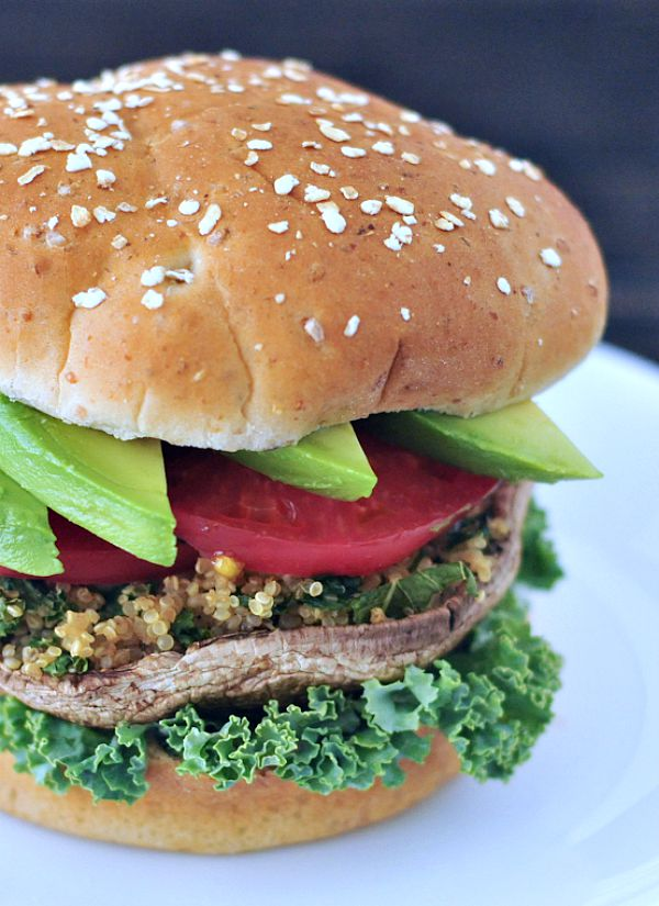 Garlic Kale Stuffed Portobello Burgers on a bun with lettuce, avocado, tomato