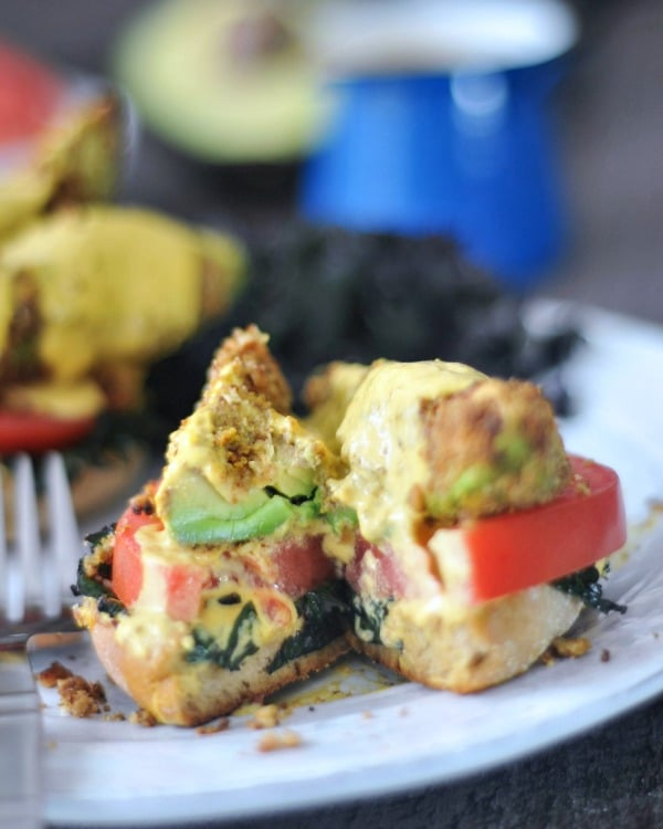 Avocado Kale Florentine with a bite sliced out: English muffin on a white plate, tomato, kale, and fried avocado on top, with hollandaise sauce poured over