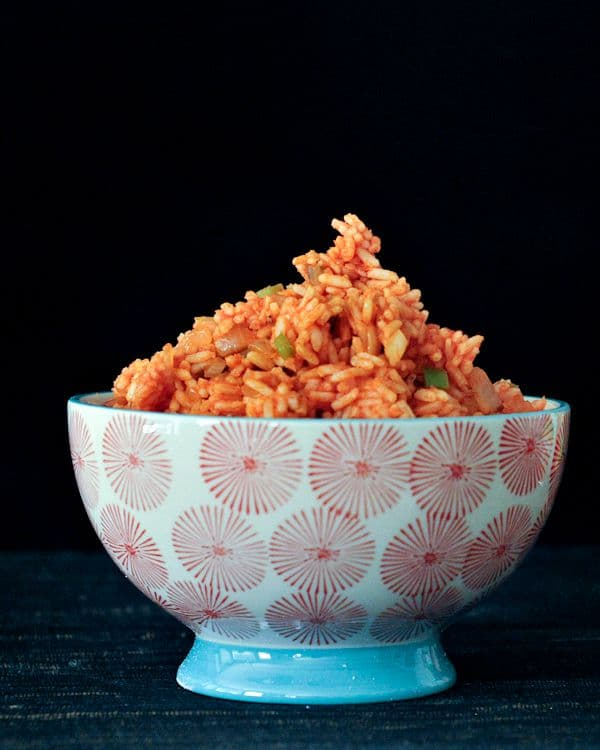 tomato red rice in a bowl, with chopped onions and green peppers