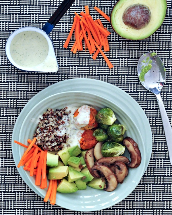 an overhead view of a Buffalo Ranch Veggie Bowl served in a light blue bowl and dish: quinoa, raw carrots, avocado cubes, sautéed mushrooms, Brussels sprouts, and vegan chicken