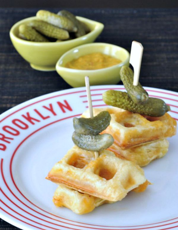 Croque Monsieur Stuffed Waffles skewered with a small pickle, on a plate