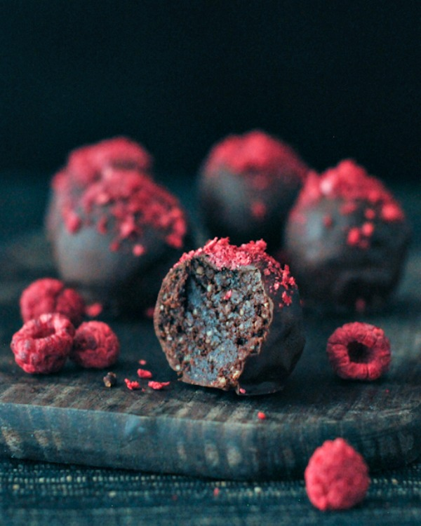 Raspberry Dusted Chocolate Fudge Brownie Truffles on a plate with dried raspberries