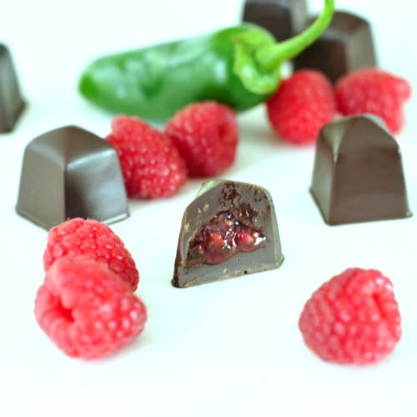 Raspberry Jalapeno Chocolates on a plate with fresh raspberries and a jalapeno pepper