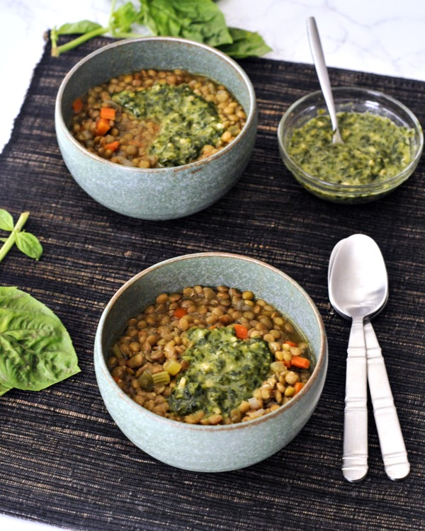 lentil soup in bowls with basil sauce on side
