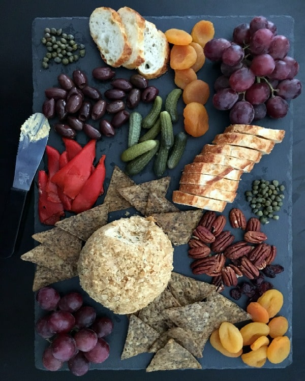 Spiced Pumpkin Basil Cheeseball served on cheese platter with baguette, chips, fruit and nuts