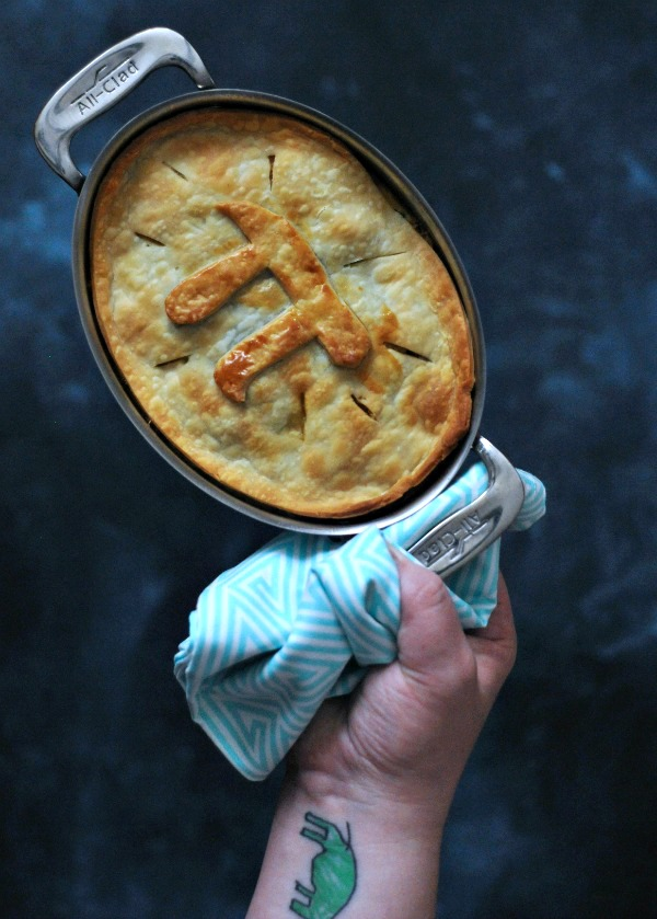 whole Jackfruit Chile Relleno Pot Pie in pan, held by one towel wrapped handle