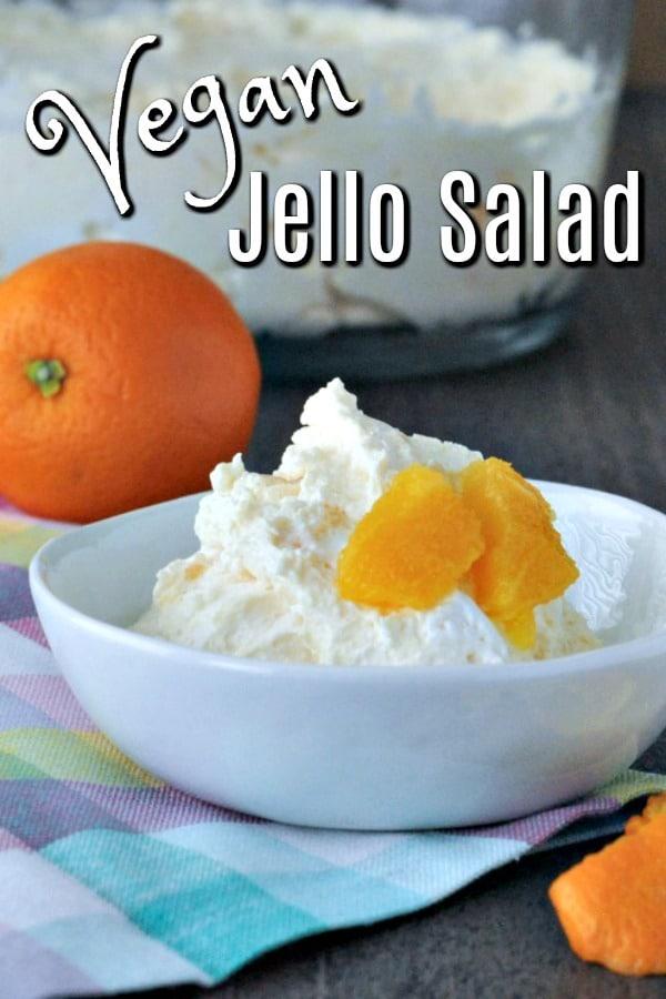 portion of Vegan Jello Salad in a small white bowl, garnished with fresh orange segments