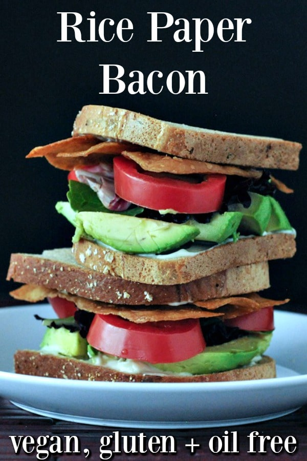 Vegan Rice Paper Bacon as part of a BLT sandwich - bread, green avocado, red tomato, bacon stacked high against a black background