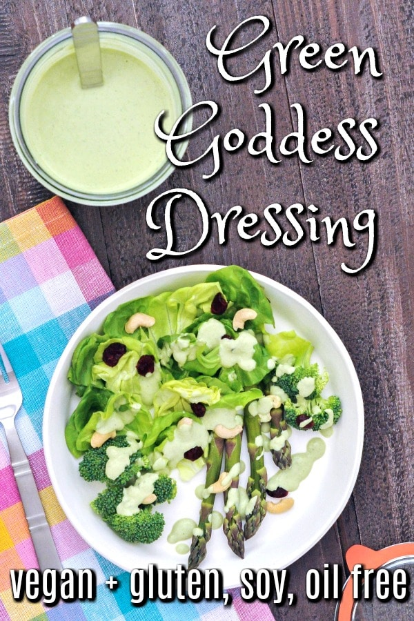 overhead view of Green Goddess Dressing in a jar and drizzled over a green salad of butter lettuce, asparagus, and cashews