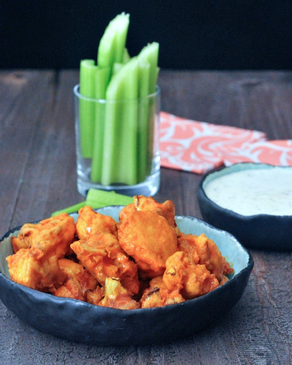 Vegan Air Fryer Buffalo Cauliflower served in a bowl with celery and ranch dressing on the side