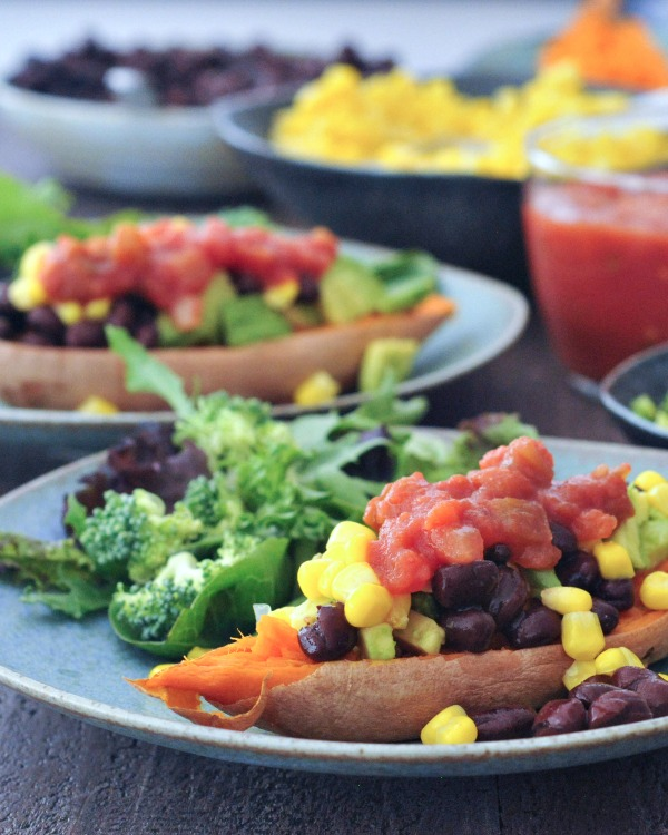 Savory Sweet Potato Breakfast Boats on plates, black bean, corn, and salsa fillings in bowls in background