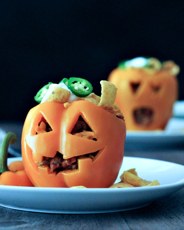two orange bell peppers carved into a halloween jack o lantern, filled with Frito pie (chili and fritos)