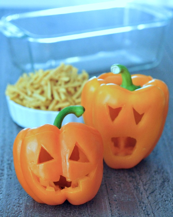 two orange bell peppers carved into a halloween jack o lanterns