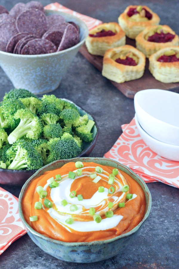 enchilada dip in bowl served with veggies and tortilla chips
