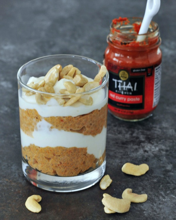 red curry coconut chia pudding and cashew cream layered in a glass, red curry paste jar in background