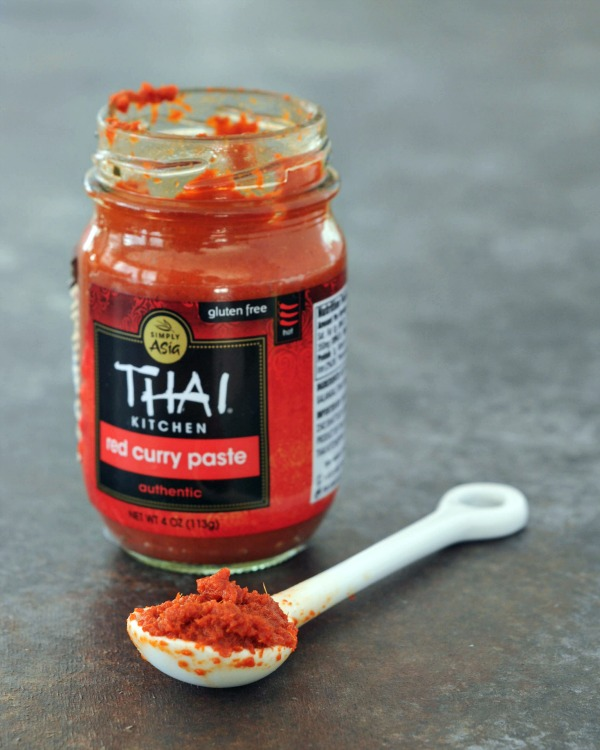 open jar of red curry paste with spoon