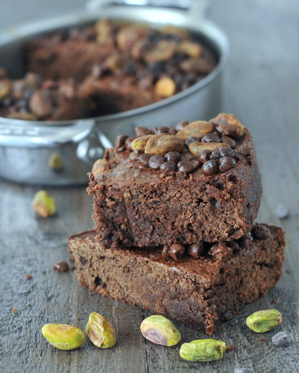 stack of Salty Pistachio Small Batch Brownies, pan in the background, pistachios scattered about