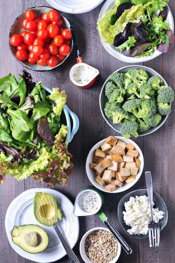 overhead view of a build your own salad bar ingredients in bowls: broccoli, tomatoes, leafy greens, tofu cubes, avocado slices, nuts, vegan cheese, and dressing.