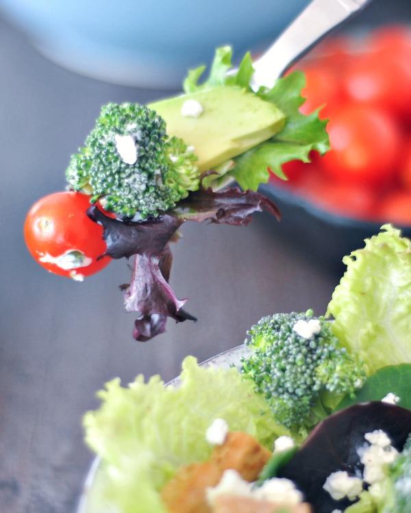a bite of salad on a fork: leaf of purple lettuce, cherry tomato, broccoli, avocado