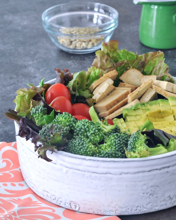 a large serving bowl of salad: greens, broccoli, tomatoes, tofu slices, avocado, nuts in a bowl on the side.
