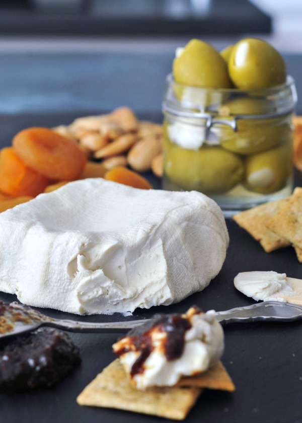 Vegan Cream Cheese on a cheese board with olives, apricots, jam and crackers