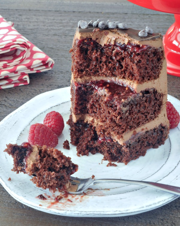 slice of Delectably Rich Vegan Chocolate Mousse Cake with several bites missing, bite of cake on fork