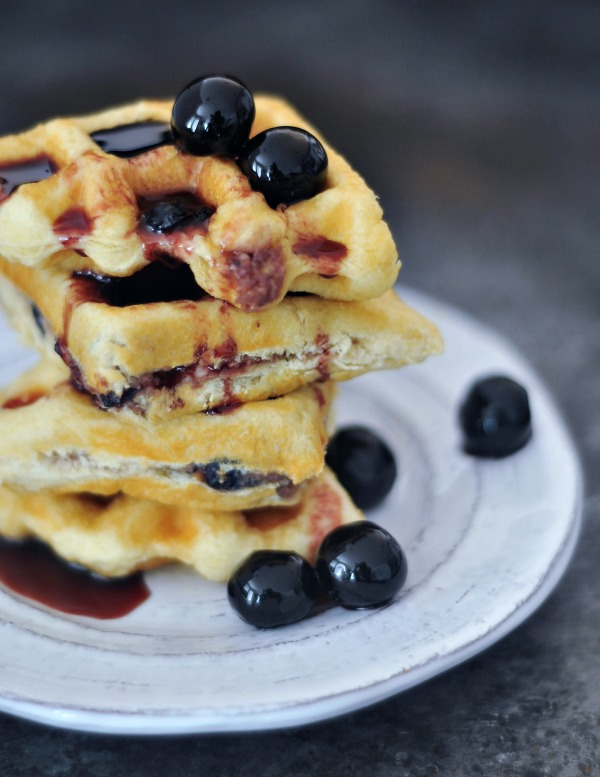 Luxardo Cheesecake Stuffed Waffles stacked on a plate with cherries and syrup