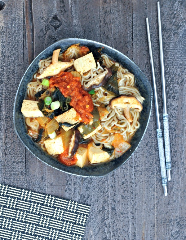 bowl of Super Flavorful Instant Kimchi Noodle Soup - tofu, mushrooms, broth, noodles, kimchi, scallions