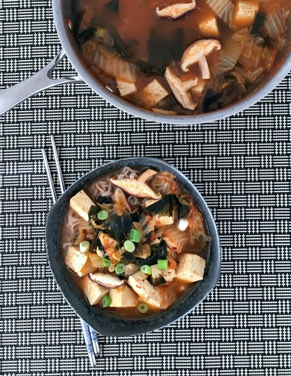 bowl and pot full of Super Flavorful Instant Kimchi Noodle Soup - tofu, mushrooms, broth, noodles, kimchi, scallions